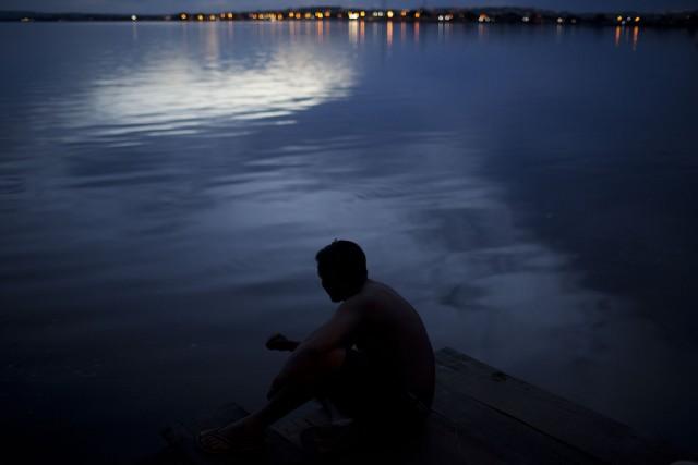 Operário que trabalha na construção de Belo Monte aproveito o final de tarde para pescar no rio Xingu próximo a Altamira